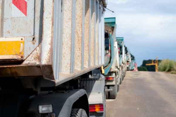 A row of dump trucks lined up alongside a road