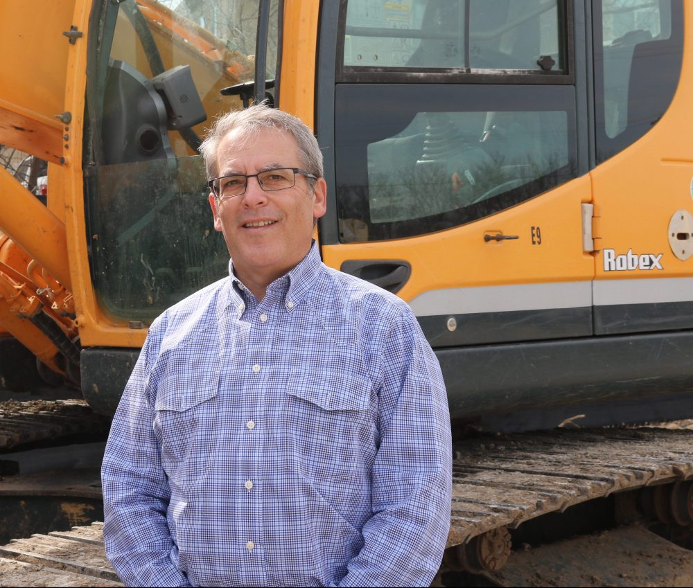 Picture of Aggregates Now owner Kirk Rovinsky who is smiling and standing next to a large piece of construction equipment
